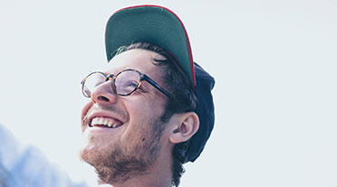 Young man smiling wearing a cap