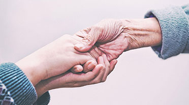 Older person holding hands with younger person