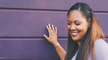 Woman touching purple wall smiling