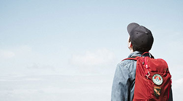 Man wearing red backpack looking up towards sky