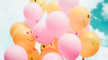 Pink and orange balloons with happy and sad faces