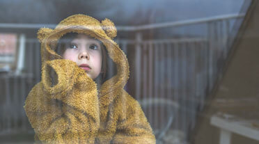 Young child in teddy bear jumper staring forlornly out of a window