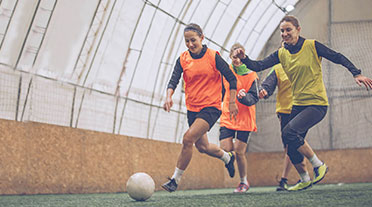 Three women playing football
