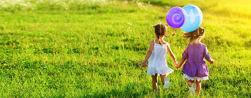 Two girls holding hands with balloons